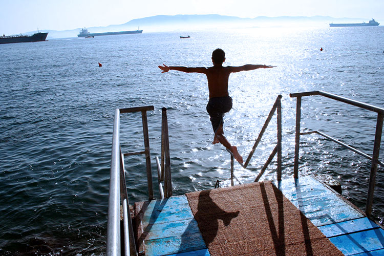 мальчик прыгает в море